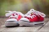 Red baby sneakers on wooden background