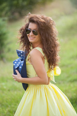 Portrait of a beautiful woman with yellow dress at the park
