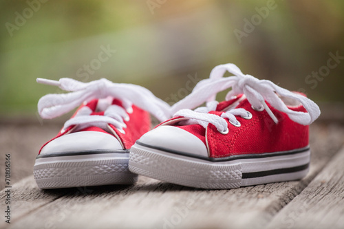 canvas print picture Red baby sneakers on wooden background