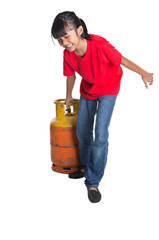 Young Asian girl moving an old cooking gas propane cylinder