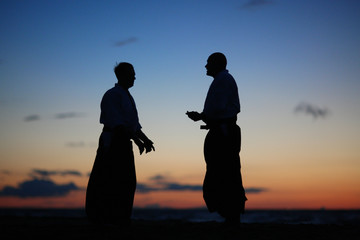 Silhouettes of two men speaking at sunset