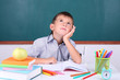 Schoolboy sitting in classroom on blackboard background