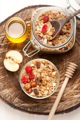 Granola with nuts, dried fruit and honey on wooden background