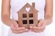 canvas print picture - Woman hands holding small house close up
