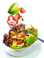 frisches Gemüse fällt in eine Salatschüssel