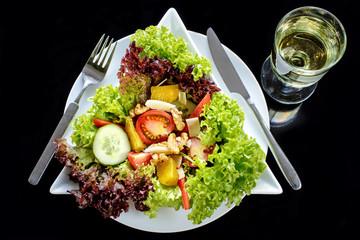 gemischter Salat mit Weißwein auf schwarz