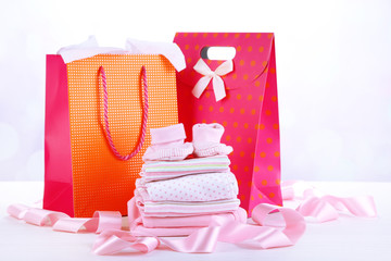 Baby clothes and gift bags on bright background