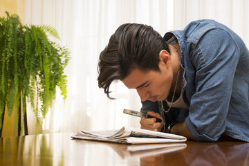 Young man reading with a magnifying glass