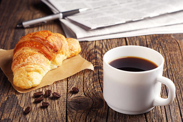 Coffee, croissant and newspaper