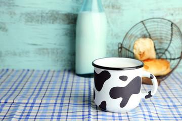 Retro mug and bottle of tasty milk, on table