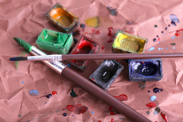 Watercolor paint cubes with brushes and spilled paint