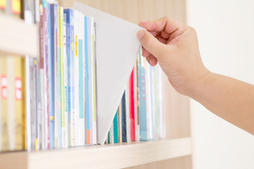 hand selecting book from a bookshelf