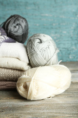 Knitting clothes and yarn on wooden background