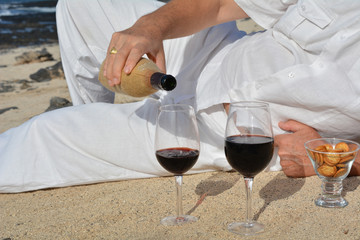 The man with a bottle of red  wine and  two glasses on the beach
