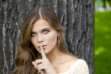 Woman has put forefinger to lips as sign of silence