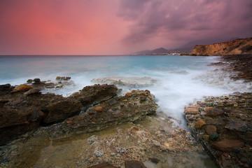 Evening storm cloud formation lit by setting sun, Crete, Greece.