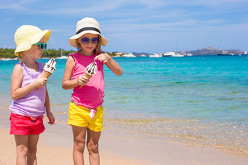 Little adorable girls eating ice cream on tropical beach
