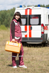 Happy paramedic female with case at ambulance machine background