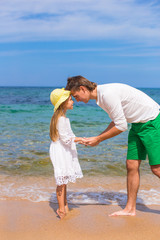Happy father and adorable little girl outdoors during beach