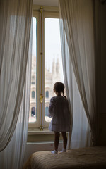 Adorable little girl looking out the window at Duomo, Milan,