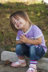 Довольный ребёнок сидит на бордюре