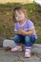 Ребёнок сидит на бордюре