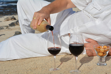 Man pouring red wine from bottle into a glass.Celebration.