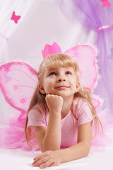 Princess girl in pink crown and butterfly wings making wishes