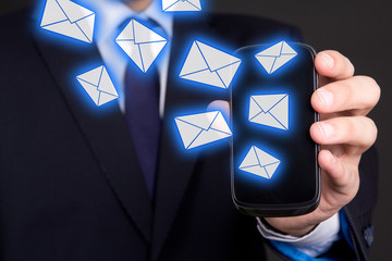 mobile phone with flying envelopes in business man hand