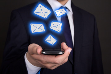 smart phone in business man hand and flying envelopes