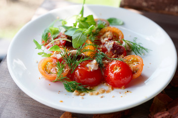 Simple appetizer with cherry tomatoes and smoked duck fillet