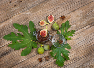 View from above of figs on fig leaf and jam  on wooden table