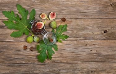 Top view of figs on fig leaf and jam  on wooden table