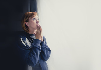 attractive woman suffering depression saying a prayer to god