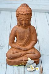 bruine Boeddha met zenstenen en bloemen