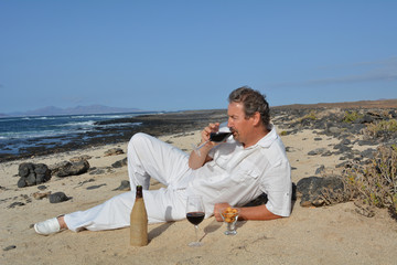 A man drinking red  wine on the tropical beach.Celebration.
