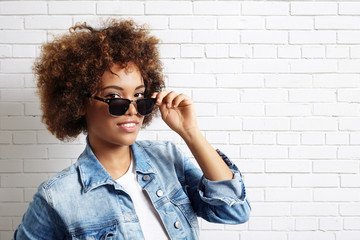 latin woman with curly hair wearing sun glasses and jeans jacket