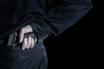 Back view of pistol being pull out of pants by male hand