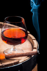 Smoking cigar and wooden brandy barrel