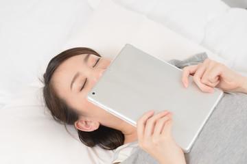 タブレットPCを持って寝落ちした女性