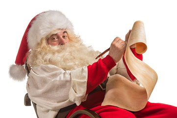 Santa Claus sitting in rocking chair and responding to letter wi
