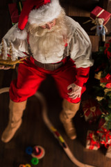 Santa Claus at home playing with new toys