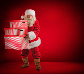 Santa Claus holding huge gift boxes