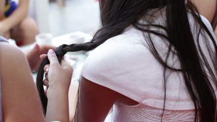 caucasian woman weaves a friend braid