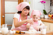 Mom and kid girl preparing cookies together at kitchen