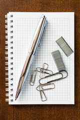 Pen on the notebook with the clips and staples