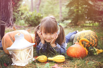 happy young brunete girl lying on the ground with pumpkins