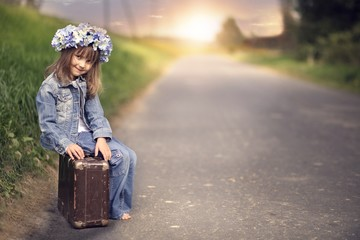 The girl in a denim jacket sitting on the road on old suitcase