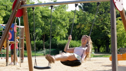 Girl in skirt on swing in summer