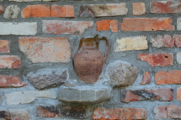 background brick wall with immured crock